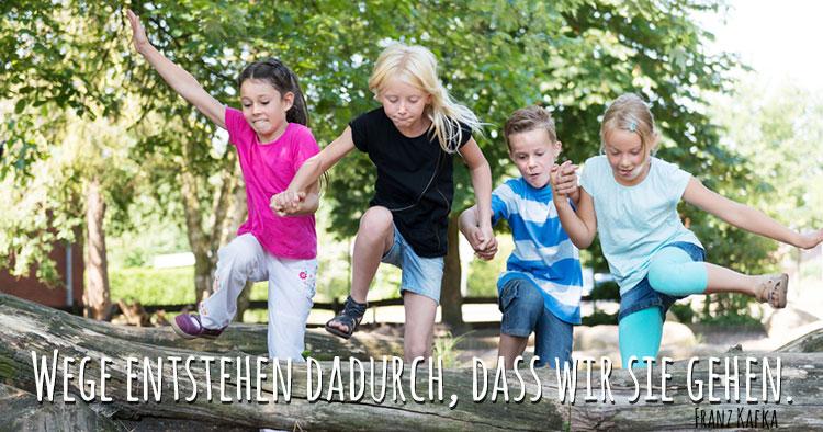 Foto von über einen Baum springenden Kindern